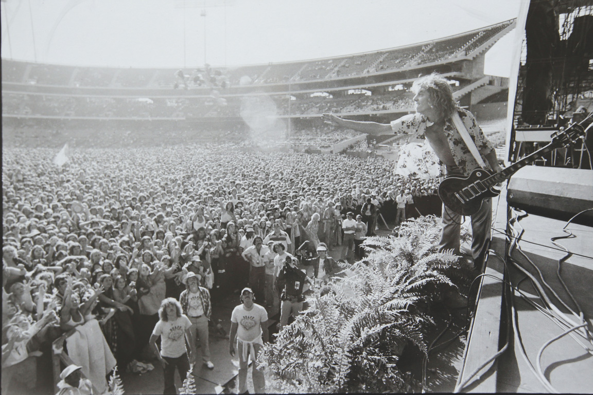 peter frampton leaning off the stage at a concert in candlestick park