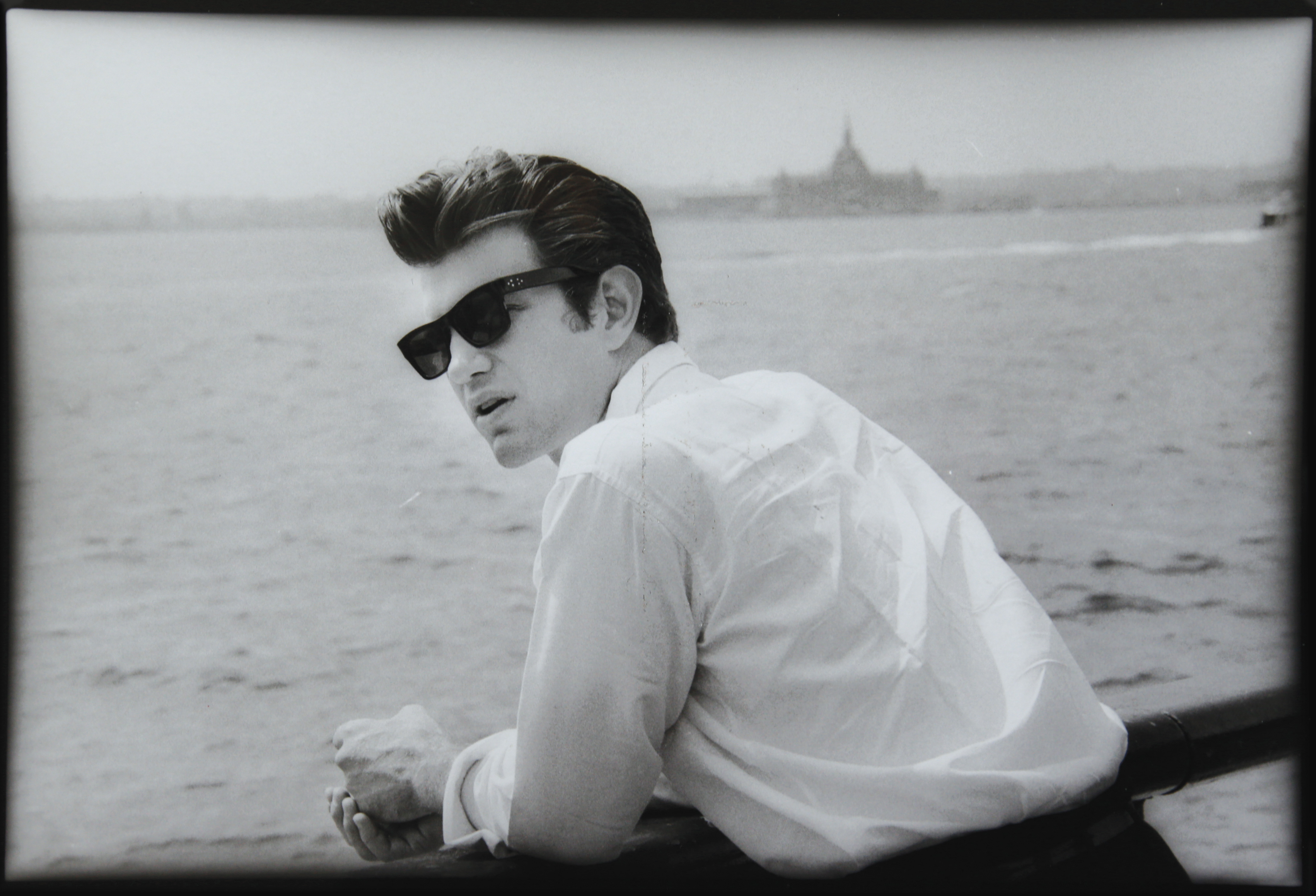 musician chris isaak leaning over a railing and looking out over the water at a wharf in New York
