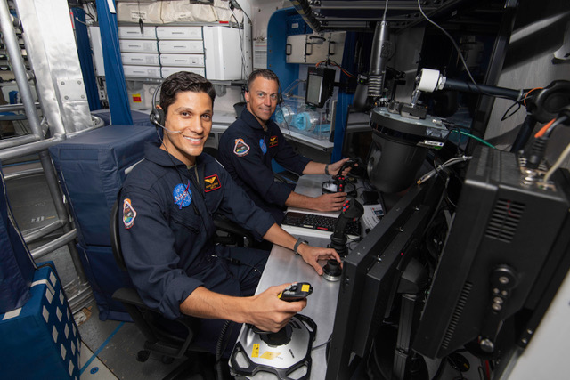 Mounir Alafrangy (left) works at the piloting station. (NASA)