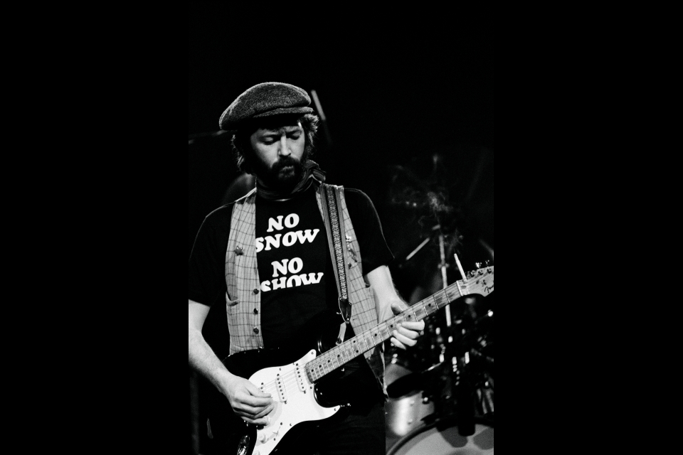 man with a beard and hat playing guitar