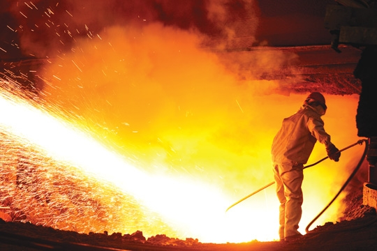 a scene from a steel mill featuring a large amount of sparks